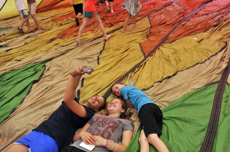 Jordan Stepke, Julia Suter and Emma Stepke photograph themselves while lying inside a hot air balloon envelope. (Kim Hairston/Baltimore Sun)