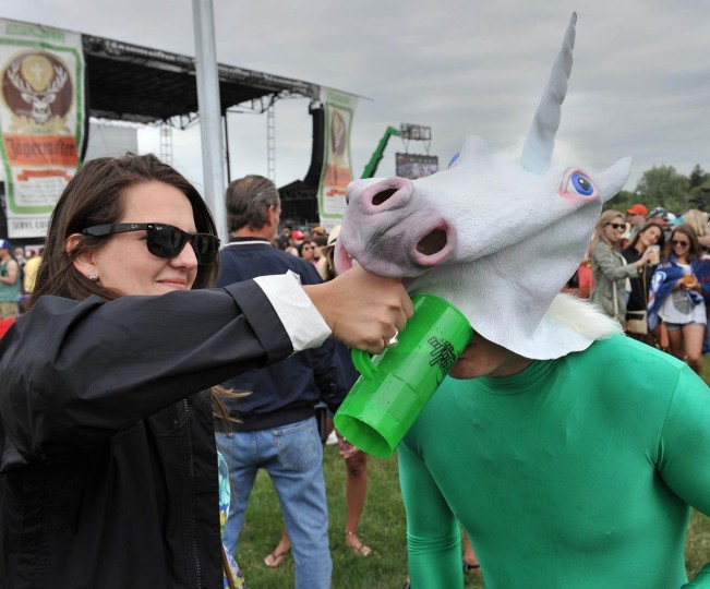 "Rebecca Skipp gives a ""unicorn"" a drink of beer in the infield at the 138th running of The Preakness at Pimlico. (Gene Sweeney Jr./Baltimore Sun)"