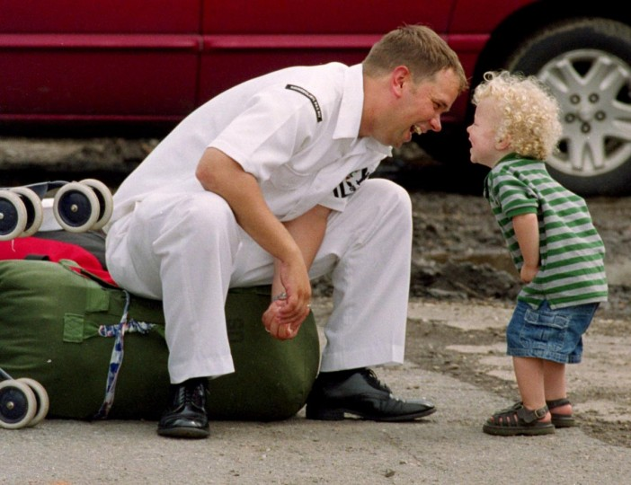 "Petty Officer Josh Cackowski smiles along with his 18-month-old son Jakob, who brought him rocks from the parking lot at Pier 11 at the Canton Marine Terminal. Photo taken June 12, 2003. According to photographer Jed Kirschbaum: The two were waiting for mom to get the car. From Duluth, Minnesota Josh is stationed at Pax River in Lexington Park, Md. The War in Iraq from the beginning worked on everyone's nerves. The homecoming of healthy sailors seemed a good respite from the all too often tragic news. I had actually finished taking pictures and started to leave when I decided to drive back to the pier to give our reporter a ride to his car. When I turned onto the pier, I saw Josh and Jakob getting ""reacquainted"" and knew it was something special. It made me smile, first when I saw it…and again when I realized I had caught some of their spirit on film."" (Jed Kirschbaum/Baltimore Sun)"