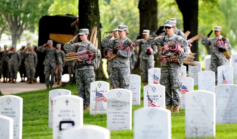 Soldiers in the Third U.S. Infantry Regiment (The Old Guard) place a small American flag one foot in front and centered before each grave marker for more than 220,000 graves during the annual Flags-In ceremony in advance of Memorial Day to honor the nation's fallen members of the military May 23, 2013 in Arlington Cemetery, Virginia. (Olivier Douliery/Abaca Press/MCT)