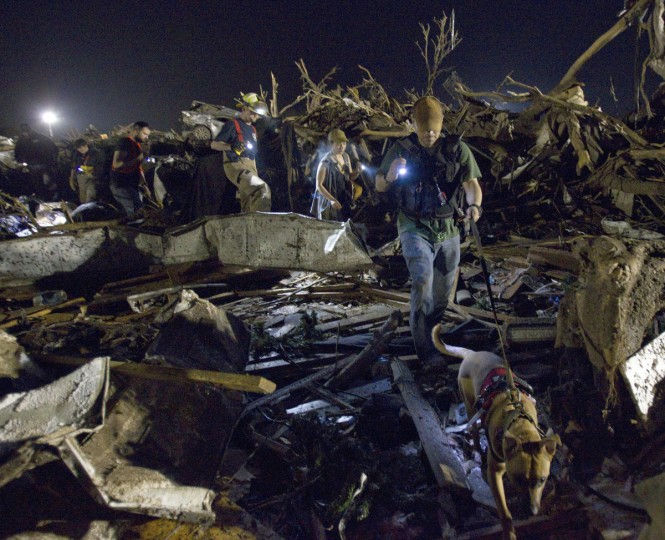Sean Satterlee follows Proxy, a Belgian malinois, through the debris, as emergency crews continued searching for victims in the early morning hours on Tuesday, May 21, 2013, in Moore, Oklahoma, after a tornado ripped through part of the town. (Shane Keyser/Kansas City Star/MCT)