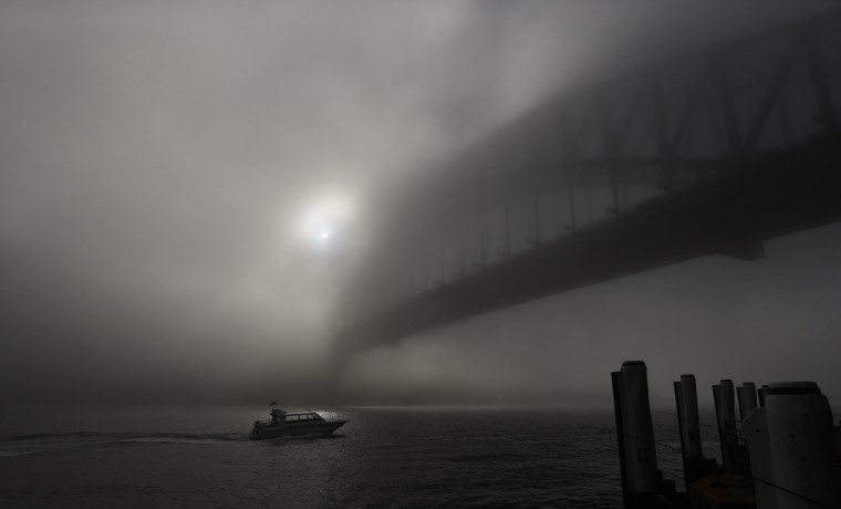 A boat navigates past the Sydney Harbour Bridge, which is covered in thick fog. Flights and ferry services were suspended and delayed on Wednesday morning after a blanket of fog covered the city for the second time in as many days, local media reported. (Daniel Munoz/Reuters)