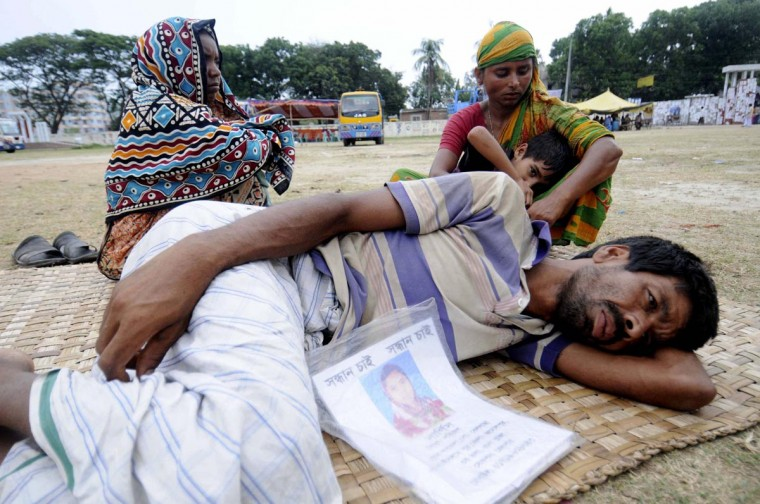 A man lies on a school ground as he waits for news on his relative, a garment worker who is still missing after the collapse of the Rana Plaza building, in Savar, outside Dhaka May 5, 2013. The wife of a Bangladeshi garment worker who was killed when a building collapsed filed a murder complaint against the building's owner on Sunday as the death toll from the country's worst industrial disaster climbed to 622. (Stringer/Reuters)