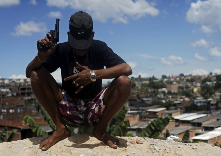 A Brazilian drug gang member nicknamed Firecracker, 22, poses with a gun atop a hill overlooking a slum in Salvador, Bahia State. One of Brazil's main tourist destinations and a 2014 World Cup host city, Salvador suffers from an unprecedented wave of violence with an increase of over 250% in the murder rate, according to the Brazilian Center for Latin American Studies (CEBELA). (Lunae Parracho/Reuters photo)