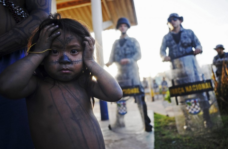 A Munduruku Indian child stands near police as Amazon Indians from different tribes occupy the main construction site of the Belo Monte hydroelectric dam in Vitoria do Xingu, near Altamira in Para State, May 28, 2013. Indians from various tribes returned to force the suspension for the second time in a month, of the dam projected to become the world's third largest in energy production, opposing it for its impact on the environment and their livelihoods. (Lunae Parracho/Reuters)