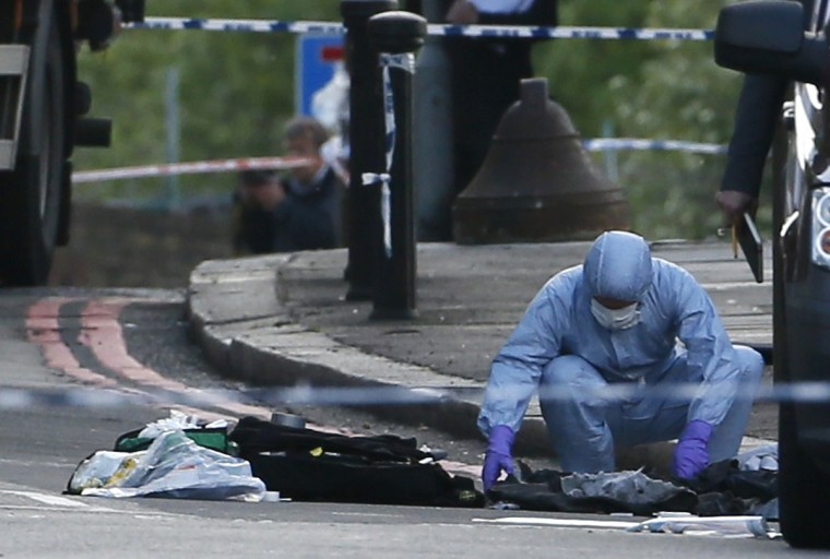 A police forensics officer investigates a crime scene where one man was killed in Woolwich, southeast London. British Prime Minister David Cameron has called a meeting of his government's emergency Cobra security committee after the killing of a man in south London, his office said on Wednesday. (Stefan Wermuth/Reuters)