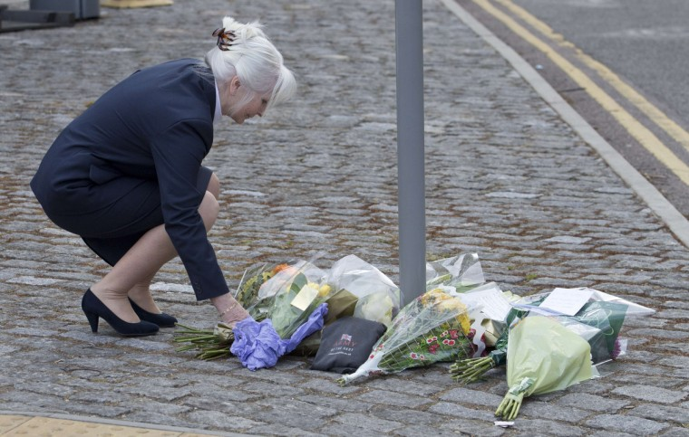 A woman places flowers outside the Royal Military Barracks, near the scene where a British soldier was killed in Woolwich, southeast London. The soldier was hacked to death on Wednesday by two men shouting Islamic slogans in a south London street, in what Prime Minister David Cameron said appeared to be a terrorist attack. (Neil Hall/Reuters photo)