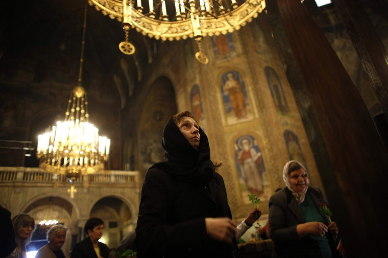"""A worshipper looks at a wooden cross during the Good Friday mass at """"Alexander Nevski"""" cathedral in Sofia. Bulgaria and other Eastern Orthodox countries celebrate Easter this weekend. (Stoyan Nenov/Reuters photo)"""