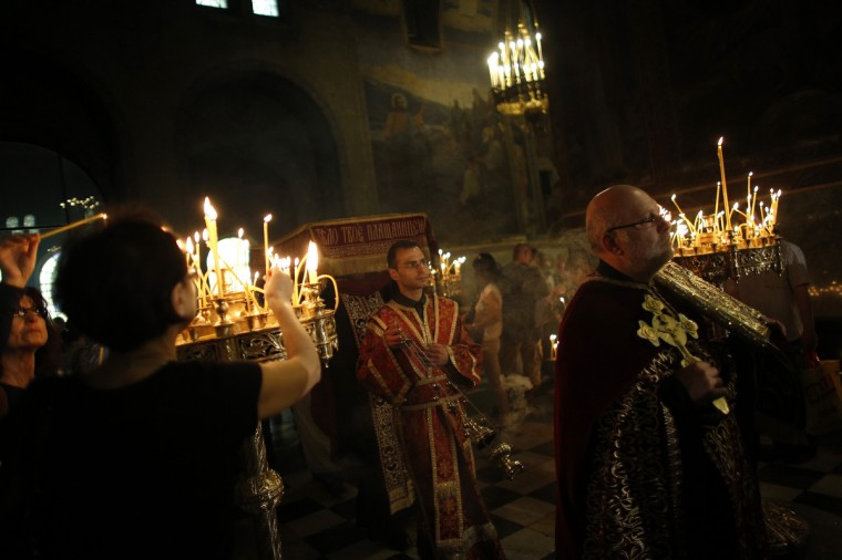 """People light candles as priests carry a procession during the Good Friday mass at """"Alexander Nevski"""" cathedral in Sofia. (Stoyan Nenov/Reuters photo)"""