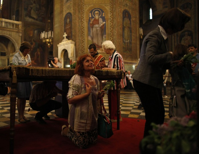 """A worshipper prays after passing under a table covered by a shroud during the Good Friday mass at """"Alexander Nevski"""" cathedral in Sofia, Bulgaria. (Stoyan Nenov/Reuters photo)"""