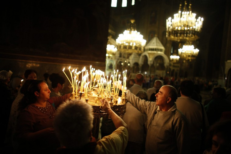 """People light candles during the Good Friday mass at """"Alexander Nevski"""" cathedral in Sofia. Bulgaria and other Eastern Orthodox countries celebrate Easter this weekend. (Stoyan Nenov/Reuters photo)"""