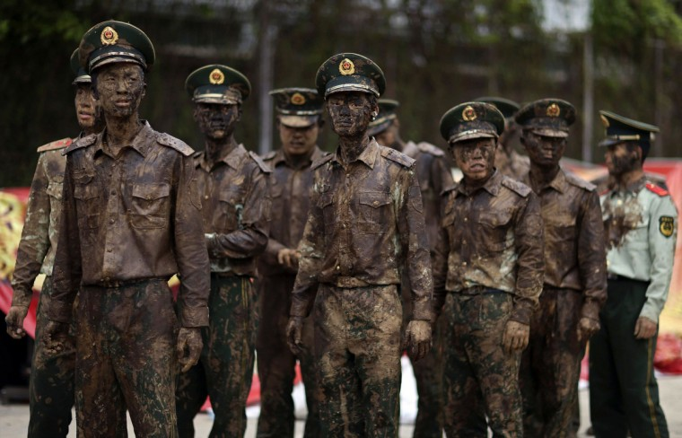 """Paramilitary policemen stand guard during """"Monihei"""" Carnival in Cangyuan county, Yunnan province. Ethnic Wa people throw and smear muddy water onto each other during the annual """"Monihei"""" festival. Wa people consider the muddy water, which contains special plant juice, sacred and as a sign of good fortune. (Wong Campion/Reuters)"""