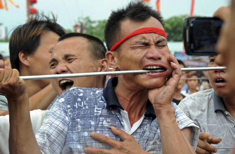 A performer has his cheek pierced with a metal rod during a festival in honour of sea goddess Mazu in Haikou, Hainan province. The three-day festival, which also includes a dragon dance performance and the display of a god statue on a water parade, ends on May 2. (China Daily)