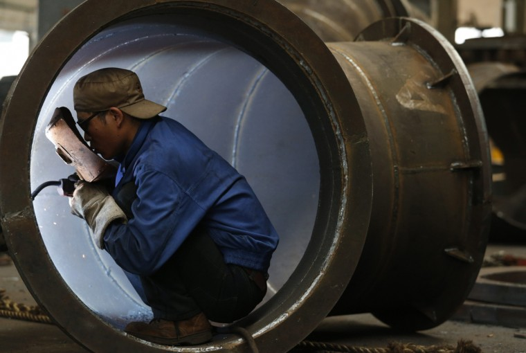 An employee welds a water turbine at a factory in Jinhua, Zhejiang province. China's factory activity shrank for the first time in seven months in May as new orders fell, a preliminary manufacturing survey showed, entrenching fears that its economic recovery has stalled and that a sharper cooldown may be imminent. (William Hong/Reuters photo)
