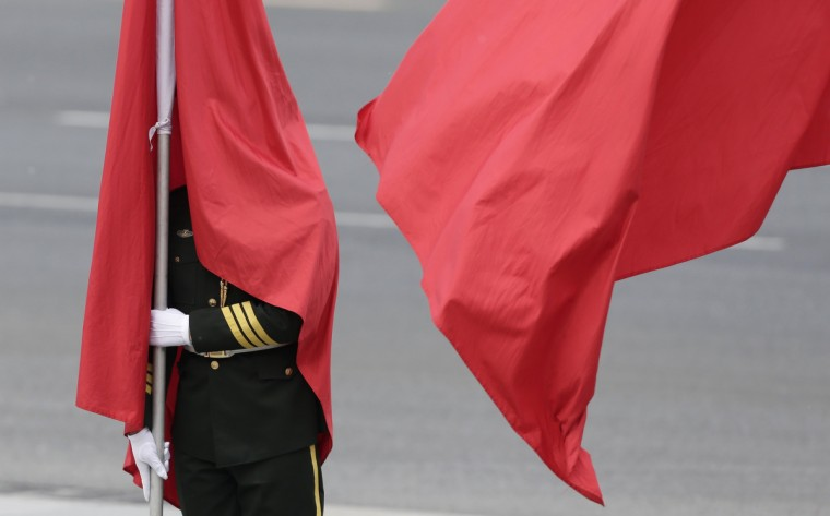 A flag is seen covering the face of an honor guard during a welcoming ceremony for the visiting Greece's Prime Minister Antonis Samaras outside the Great Hall of the People in Beijing. (Jason Lee/Reuters photo)