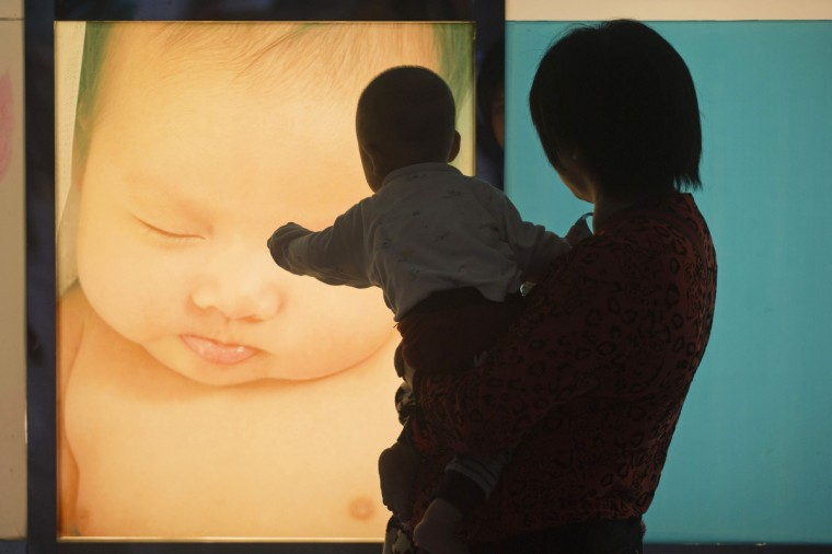 A baby reacts in front of a poster at the Guangzhou Women and Children's medical centre in the southern Chinese city of Guangzhou. With China's first breast milk bank opening in June at the centre, about 80 moms have donated to premature babies and other needy infants since the trial period started in late March, local media reported. (Tyrone Siu/Reuters)