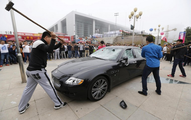 Men smash a Maserati with hammers outside the Qingdao International Automobile Exhibition in Qingdao, Shandong province. One of the men smashing the Maserati said the car owner had asked them to destroy the car, which costs around 2,600,000 yuan ($423,280), in protest against bad after sales service provided by a dealership store. The store had charged the owner the price of a new part despite repairing the Maserati with an old part, according to Xinhua News Agency. (Reuters)
