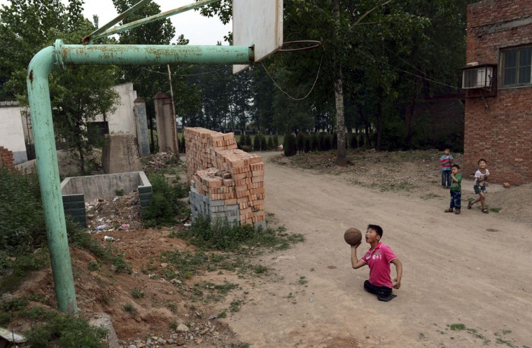 Basketball fan Qin Xulei prepares to shoot a basketball into a hoop outside his home in Yichuan county, Luoyang, Henan province, China May 15, 2013. Qin, 13, who is among the top ten students at his school, lost his legs in a car accident when he was three. Qin hopes to represent China as part of their national wheelchair basketball team in the Paralympic Games in the future. (Stringer/Reuters)