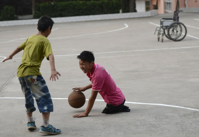 Basketball fan Qin Xulei (R) dribbles a basketball as he plays against his friend at a middle school in Yichuan county, Luoyang, Henan province, China May 15, 2013. Qin, 13, who is among the top ten students at his school, lost his legs in a car accident when he was three. Qin hopes to represent China as part of their national wheelchair basketball team in the Paralympic Games in the future. (Stringer/Reuters)