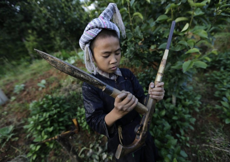 Ethnic Miao boy Gun Diuliang, 10, knocks his gun with the back of a knife to tamp down the gunpowder before a shooting practice in the village of Basha in Congjiang county, Guizhou province, May 21, 2013. (Jason Lee/Reuters)