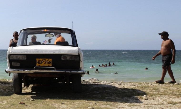 A man walks near a parked car beside the sea on the outskirts of Havana May 19, 2013. (Desmond Boylan/Reuters)