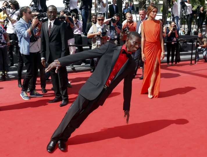 "Cast member Souleymane Deme (C) performs on the red carpet as he arrives with director Mahamat-Saleh Haroun (L) and cast member Anais Monory for the screening of the film ""Grigris"" in competition during the 66th Cannes Film Festival in Cannes. (Jean-Paul Pelissier/Reuters)"