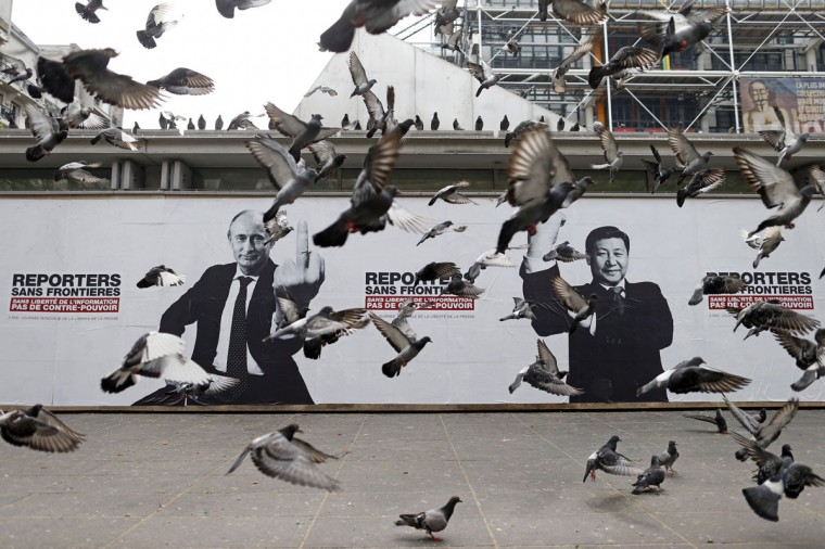 Pigeons fly past a poster depicting Russian President Vladimir Putin and his Chinese counterpart Xi Jinping (R) pasted on the Brancusi Atelier by activists from Reporters Without Borders (RSF) to mark the 20th annual World Press Freedom day in Paris. The slogan reads, 'Without freedom of information, no counter-power.' (Benoit Tessier/Reuters)