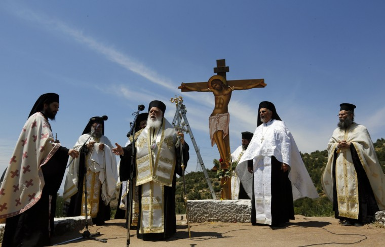 Greek Orthodox priests conduct a liturgy in front of a figure of a crucified Jesus Christ on Good Friday at Penteli monastery north of Athens. (Yannis Behrakis/Reuters photo)