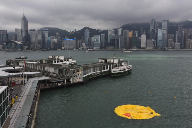 A deflated Rubber Duck by Dutch conceptual artist Florentijn Hofman floats on Hong Kong's Victoria Harbour. The 16.5-meter-high inflatable sculpture, which made its first public appearance in the territory on May 2, will be shown at the Ocean Terminal for a month. The Rubber Duck was deflated after some of its parts broke. (Tyrone Siu/Reuters)