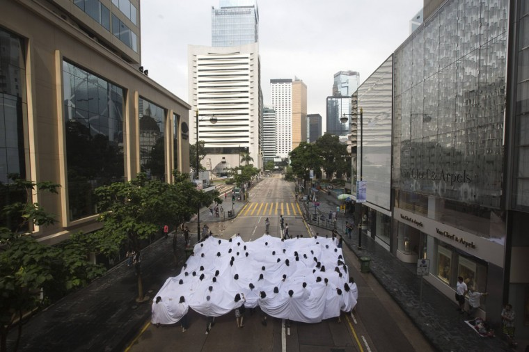 """People with their heads sticking out from holes on a large white cloth take part in """"Divisor"""", a performance art piece by Brazilian artist Lygia Pape, during the exhibition entitled """"A Journal of the Plague Year. Fear, ghosts, rebels. SARS, Leslie and the Hong Kong story"""" at Hong Kong's financial central district. (Tyrone Siu/Reuters)"""