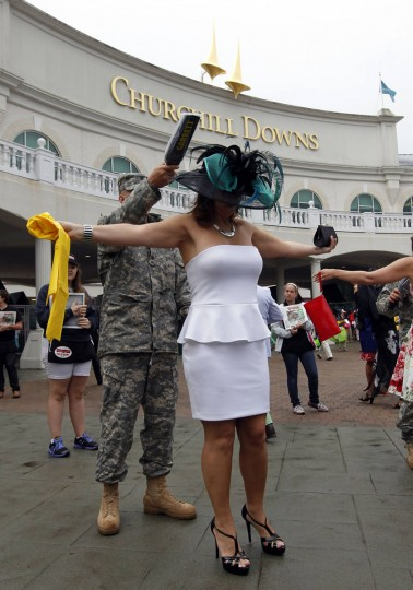 A military person uses a security wand over a patron as she enters Churchill Downs before the running of the 139th Kentucky Derby horse race in Louisville, Kentucky. (John Sommers II/Reuters)