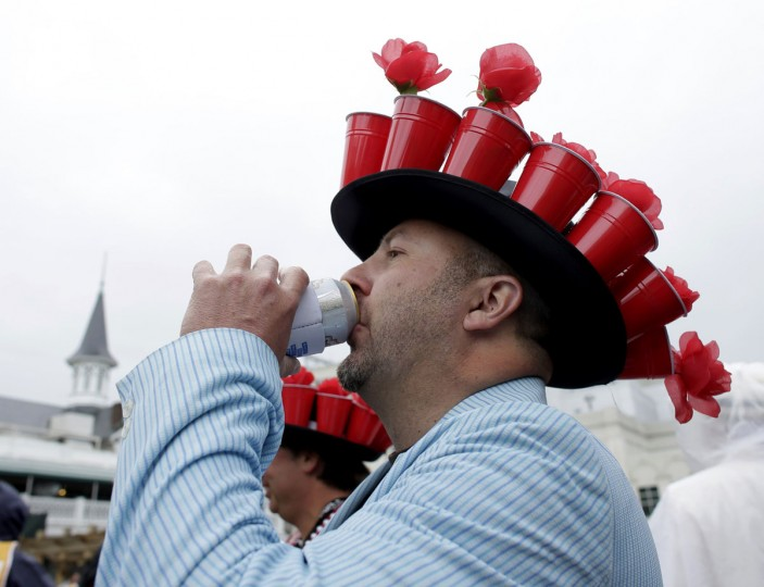 Race patron Andre Broussard enjoys a drink under his hat of red beer cups filled with flowers before the running of the 139th Kentucky Derby horse race at Churchill Downs in Louisville, Kentucky. (John Gress/Reuters)