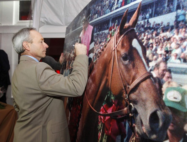 Jockey Steve Cauthen signs a pictures of himself on the horse Affirmed before the running of the 139th Kentucky Derby horse race at Churchill Downs in Louisville, Kentucky. Cauthen is the last jockey to have won the Triple-Crown, riding Affirmed in 1987. (Matt Sullivan/Reuters)