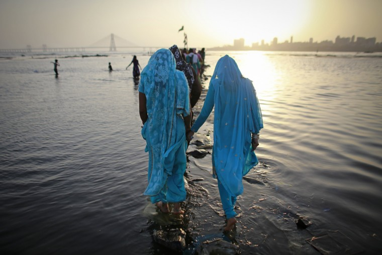 Devotees walk on a pathway made of cement bags to offer prayers at a shrine along the Arabian Sea in Mumbai May 9, 2013. (Danish Siddiqui/Reuters photo)