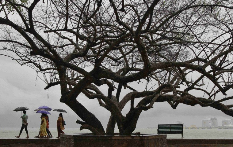 Beachgoers stroll along the Fort Kochi beach while holding umbrellas during a rain shower in the southern Indian city of Kochi. India's weather office has forecast an average monsoon in the country in 2013. (Sivaram V/Reuters)