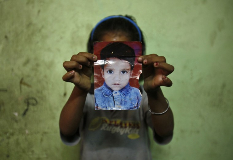 Mansi, 7, poses with a photograph of her missing three-year-old sister Muskaan inside their house in New Delhi. Muskaan went missing while playing in the neighbourhood on October 30, 2010, according to her family. Between January 1 and May 8, 2013, 725 children in Delhi were reported missing and are untraced, according to data from India's Zonal Integrated Police Network website. (Mansi Thapliyal/Reuters photo)