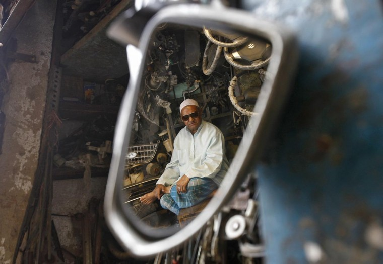 A man selling used vehicle spare parts is reflected in a mirror as he sits inside his shop in the old quarters of Delhi May 13, 2013. (Mansi Thapliyal/Reuters)