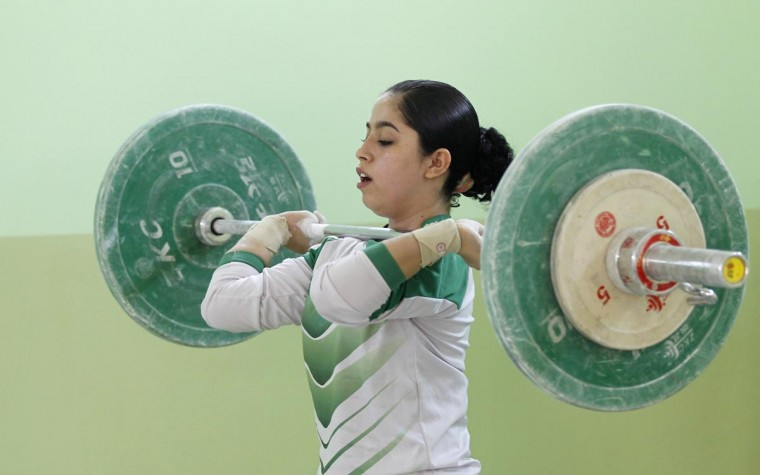 An Iraqi weightlifter lifts a loaded barbell during training session at a gym in Sadr city in Baghdad, April 28, 2013. (Mohammed Ameen/Reuters)
