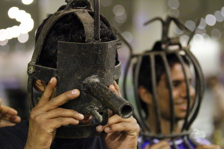 Visitors try on metal masks, used as torture devices by the regime of Iraq's ousted leader Saddam Hussein, at an exhibition gallery at the Martyrs Monument in Baghdad. The monument, also known as the al-Shaheed Monument, was built during Saddam Hussein's reign and is dedicated to Iraqi soldiers who died in the Iran-Iraq war. (Thaier al-Sudani/Reuters)