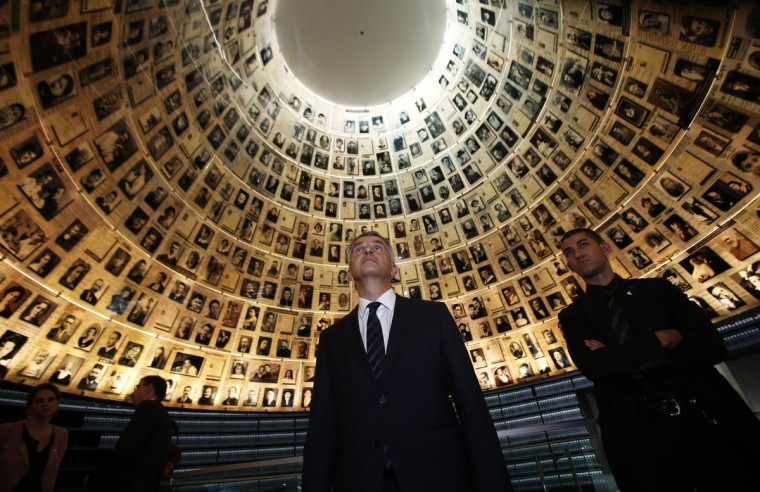 Swiss Foreign Minister Didier Burkhalter (C) looks at pictures of Jews killed in the Holocaust, during a visit to the Hall of Names at Yad Vashem's Holocaust History Museum in Jerusalem. (Baz Ratner/Reuters photo)