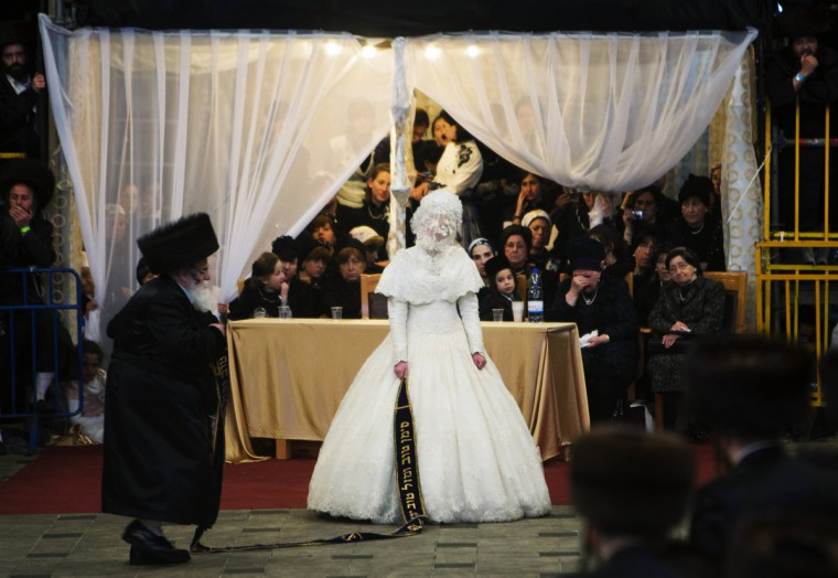 Ultra-Orthodox Jewish bride Hannah Batya Penet dances with her relative during a wedding ceremony in Jerusalem. Some 25,000 people gathered to celebrate the wedding of Penet to Shalom Rokeach, the eldest grandson of the Chief Rabbi of Belz, Yissachar Dov Rokeach, according to local media. The Belz Hasidic dynasty is one of the largest Hasidic movements in the world. (Ronen Zvulun/Reuters)