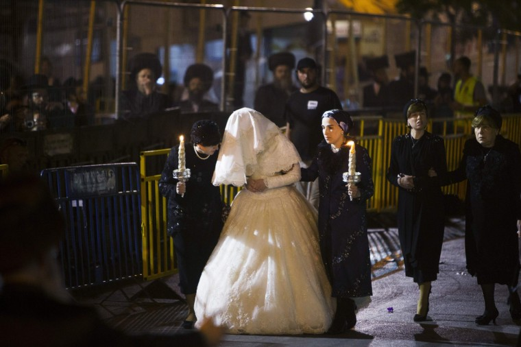 Ultra-Orthodox Jewish women walk with Hannah Batya Penet, the bride of Shalom Rokeach, grandson of the Chief Rabbi of Belz, during a wedding ceremony in Jerusalem. Some 25,000 people gathered on Tuesday to celebrate the wedding of Rokeach, the eldest grandson of the current leader of the Belz Hasidic dynasty Yissachar Dov Rokeach, who heads one of the largest Hasidic movements in the world, according to local media. (Ronen Zvulun/Reuters)