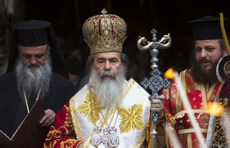 Greek Orthodox Patriarch of Jerusalem Metropolitan Theophilos (C) stands at the beginning of the washing of the feet ceremony outside the Church of the Holy Sepulchre in Jerusalem's Old City. (Ronen Zvulun/Reuters photo)