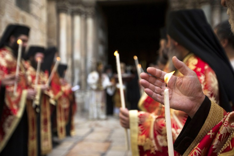 Greek Orthodox priests hold candles as they wait for the Greek Orthodox Patriarch of Jerusalem Metropolitan Theophilos to exit the Church of the Holy Sepulchre in Jerusalem's Old City, at the beginning of the washing of the feet ceremony ahead of Orthodox Easter. (Ronen Zvulun/Reuters photo)