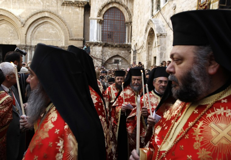 Greek Orthodox priests hold candles during the washing of the feet ceremony outside the Church of the Holy Sepulchre in Jerusalem's Old City. (Ammar Awad/Reuters photo)