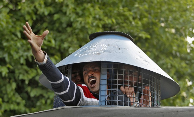A government employee shouts slogans from inside a police vehicle after he was detained by police during a protest in Srinagar May 8, 2013. Indian police detained dozens of employees on Wednesday during a protest demanding a greater regularization of temporary jobs and a hike in salary, according to protesters. (Danish Ismail/Reuters)