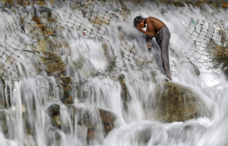 A boy bathes in a stream at Dara on the outskirts of Srinagar. (Danish Ismail/Reuters photo)