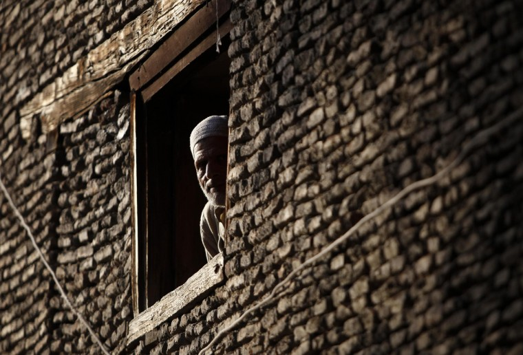 A Kashmir man looks through the window of his house in downtown Srinagar. (Danish Ismail/Reuters photo)