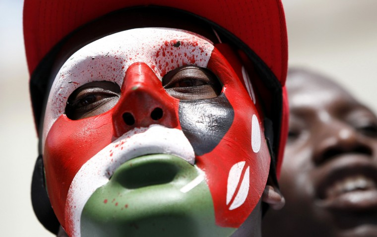 A protestor wearing a mask with the colors of the Kenyan flag participates in a demonstration against lawmakers' salary demands outside the parliament buildings in the capital Nairobi. Kenyan police in riot gear fired teargas and water cannons on Tuesday to disperse about 200 protesters gathered outside parliament to demonstrate against lawmakers' salary demands.(Thomas Mukoya/Reuters)