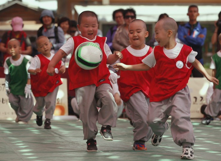 Boys, who are experiencing the lives of Buddhist priests by staying in a temple for two weeks as novice monks, compete with each other for the ball during a friendly soccer match to celebrate the upcoming birthday of Buddha at Jogye temple in Seoul. Buddha's birthday falls on May 17 in South Korea. (Kim Hong-Ji/Reuters)